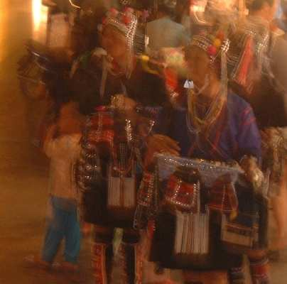 ARTSY SHOT, OR LUCKY MISTAKE?   Whatever, this blurry shot of some Akha women (and child), on a busy Chiang Mai street at night, has a sort of, well, QUALITY to it... doesn't it?!    :=)