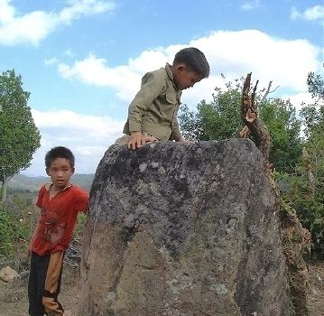 Two local boys, one climbing a fairly large stone 'jar'