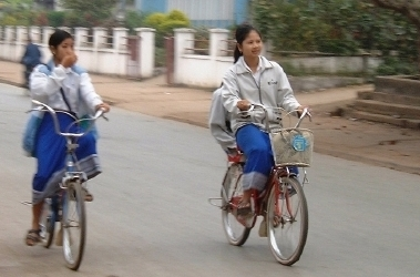 Young Lao women, or school girls, zipping along on their bikes