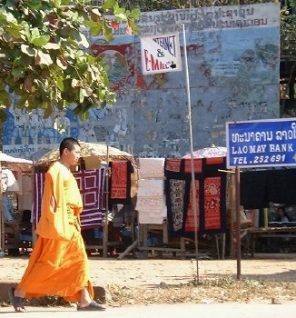 Yes, you probably recognize this one, from the homepage.  It's obviously a monk, walking by on Thanon Phothisalat (Phothisalat Street, a main thorougfare thru town) near signs representing both the present (a bank, email) and past (old, peeling revolutionary billboard).