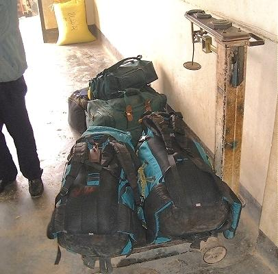 Our backpacks, being weighed at the Phonsavan airport--the old fashioned way