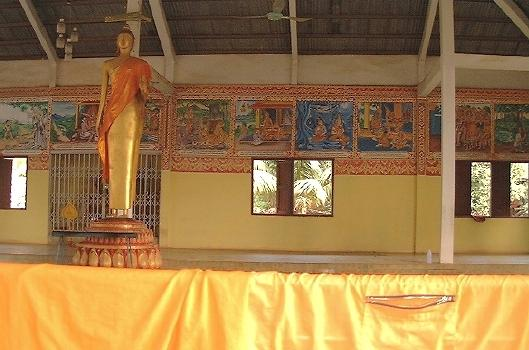 Wat Phonxai (Vientiane): an open-air part of the wat, with a standing Buddha statue, and a monk's garment drying off on the railing